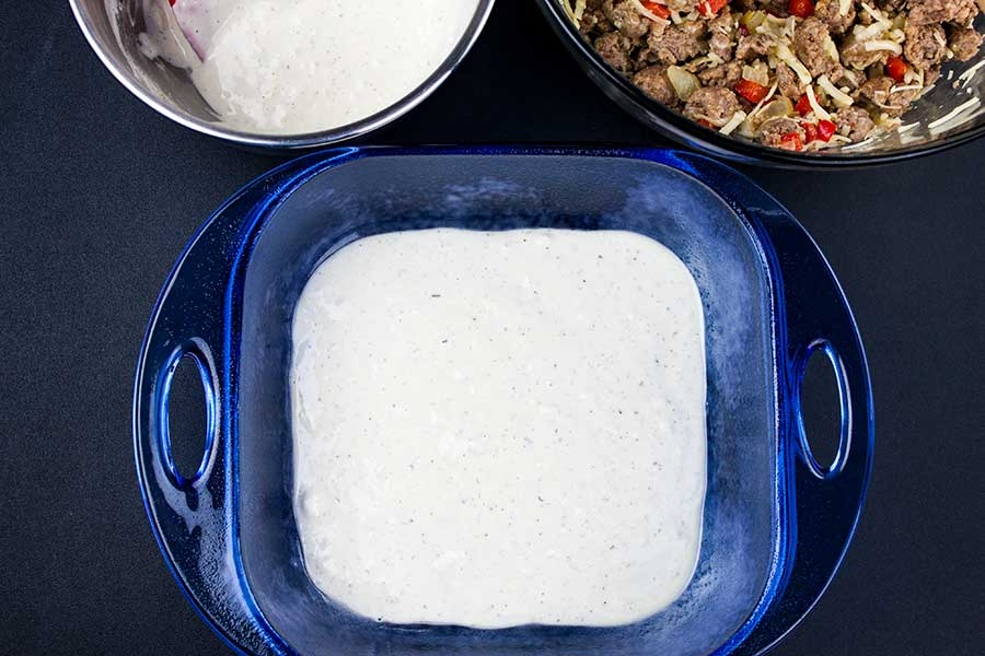 Sausage Breakfast Cake Recipe - first layer of batter in the bottom of a blue glass pan