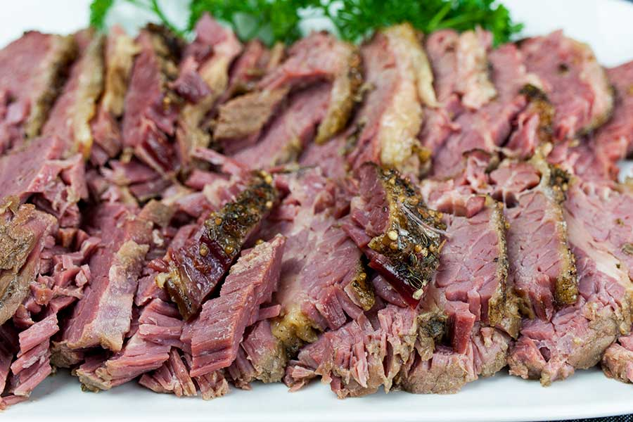 Slow Cooker Corned Beef - sliced corned beef on a white platter garnish with fresh parsley
