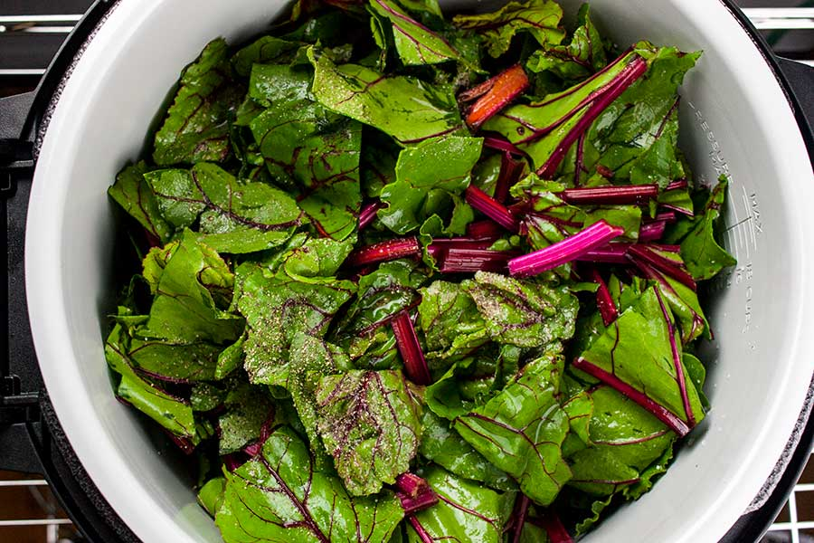 beet greens in the pot of the Ninja Foodi seasoned with salt and pepper