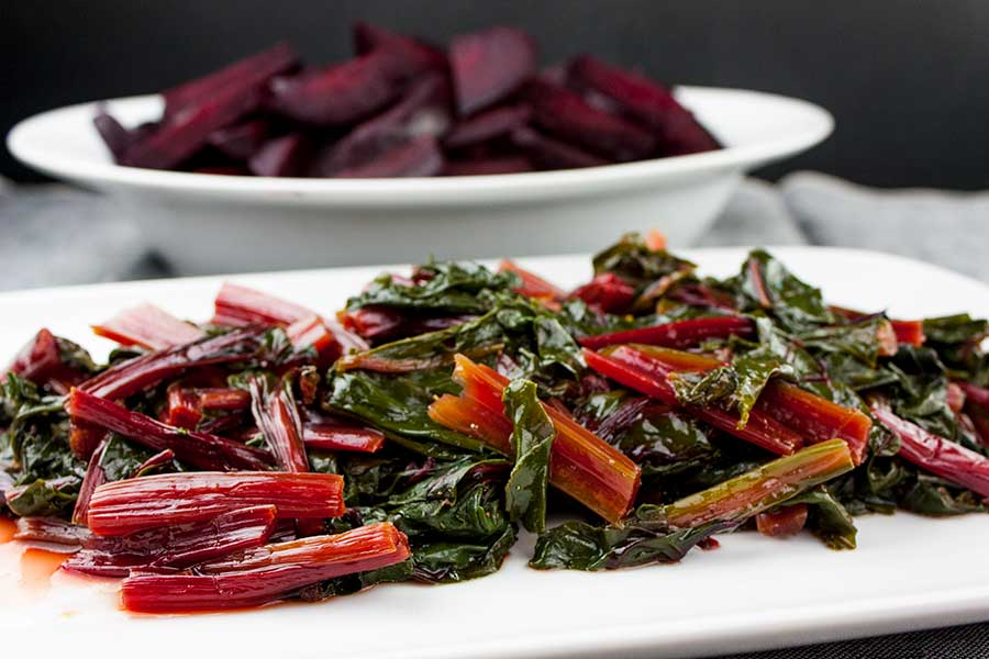cooked Fresh Beet Greens on a white platter with cooked beets in a white serving platter in the background