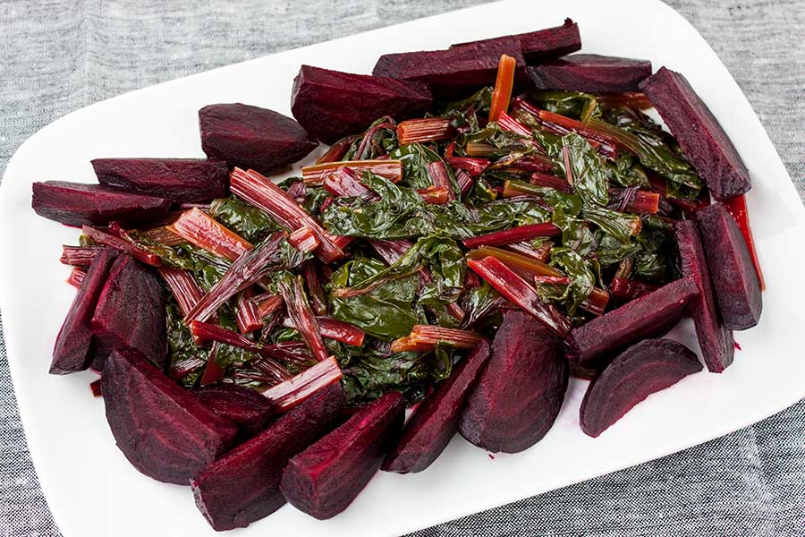 cooked beet greens on a white platter surrounded by cooked beets