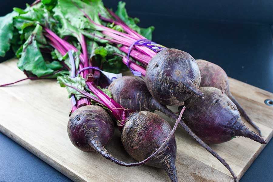 fresh beets with greens attached on a wooden cutting board