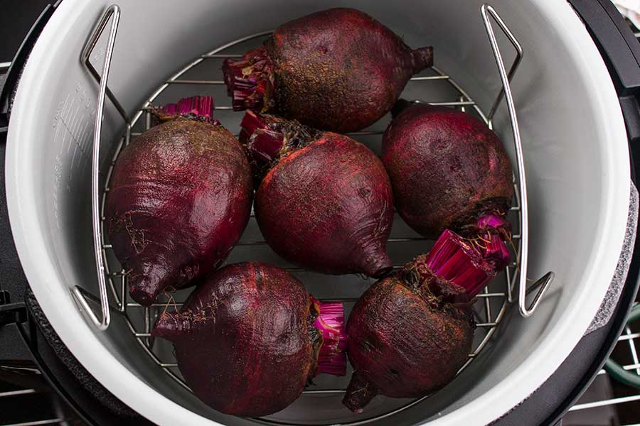 raw beets with greens removed on the lower rack in the Ninja Foodi pot