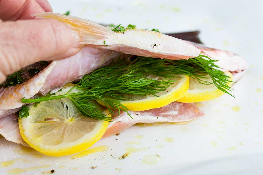 closeup of herbs and lemons slices stuffed into the cavity of a red snapper