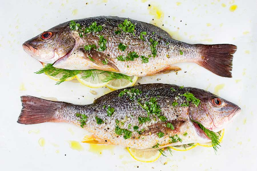 two whole red snappers prepped with herbs and seasonings on a parchment paper lined baking sheet