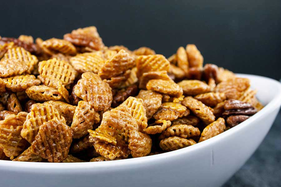 closeup of the Praline Crunch Snack Mix in a white serving bowl