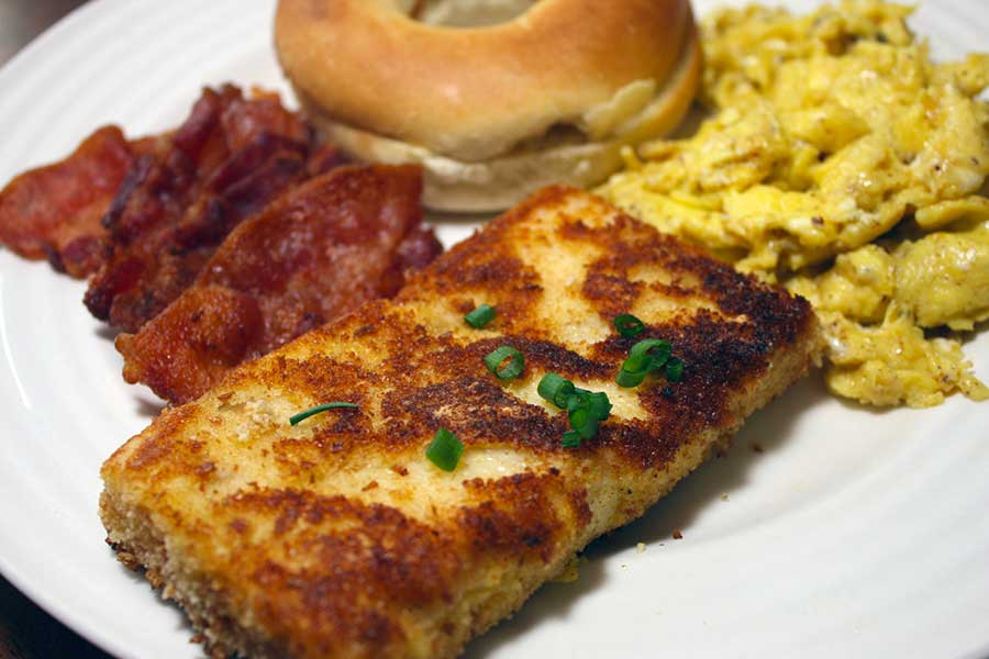 Fried Grit Cakes on a white plate with bacon, scrambles eggs, and a bagl