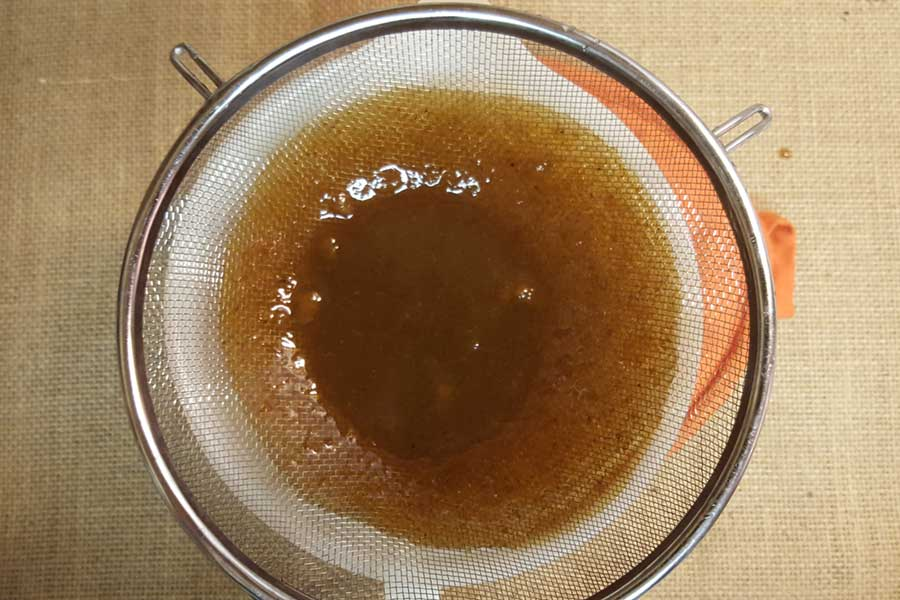 pumpkin spice syrup in a strainer