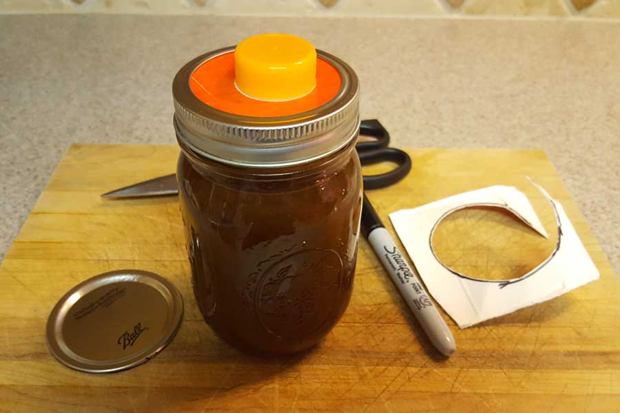 mason jar filled with pumpkin spice syrup with the orange juice spout inserted under the lid ring
