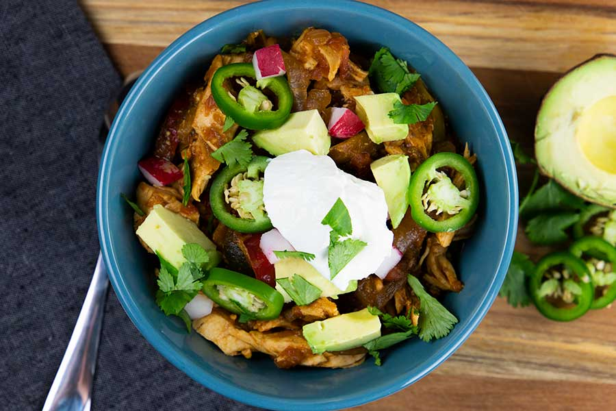 Chicken fajita stew topped with jalapeños, avocado, cilantro and chopped radish in a blue bowl