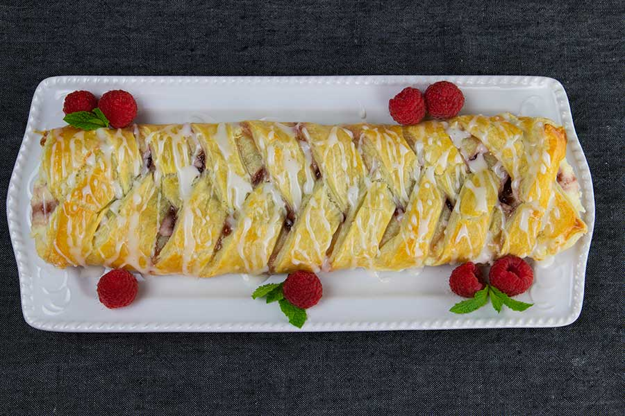Raspberry Cream Cheese Danish - baked danish on a white serving dish garnished with fresh raspberries and mint