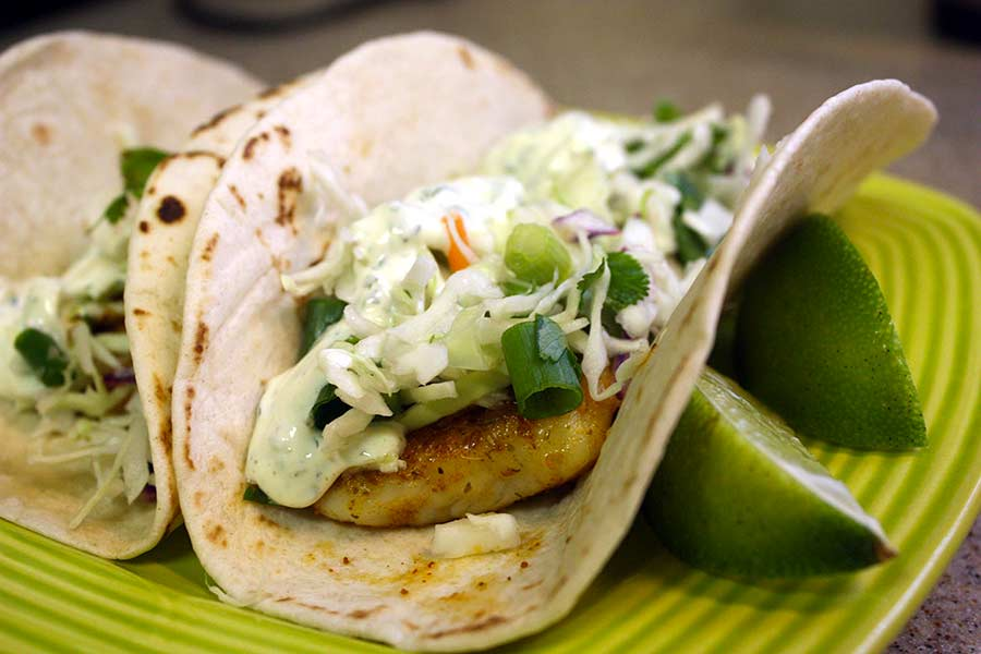 Fish tacos on a green plate with lime wedges