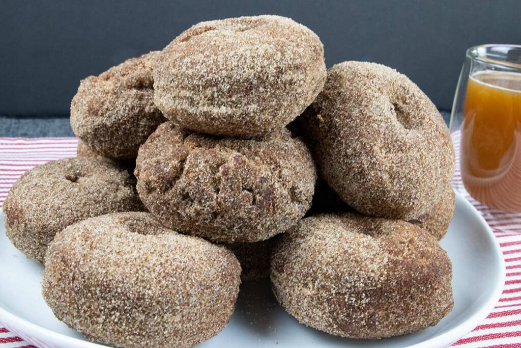 apple cider donuts stacked on a white plate