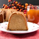 slice of apple cider pound cake on white plate with red dots