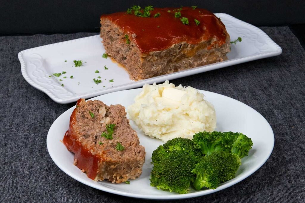 Meatloaf with mashed potatoes and broccoli on a white plate.