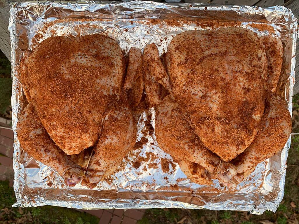 Two raw chickens with rub.