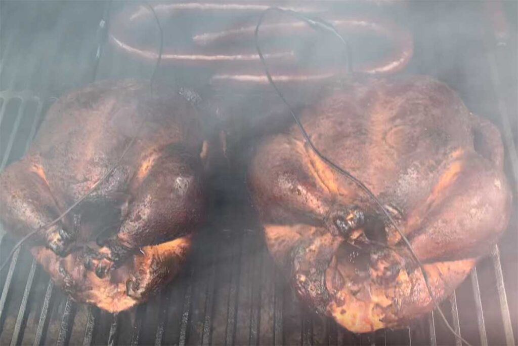 Two smoked chickens in the smoker with sausage.