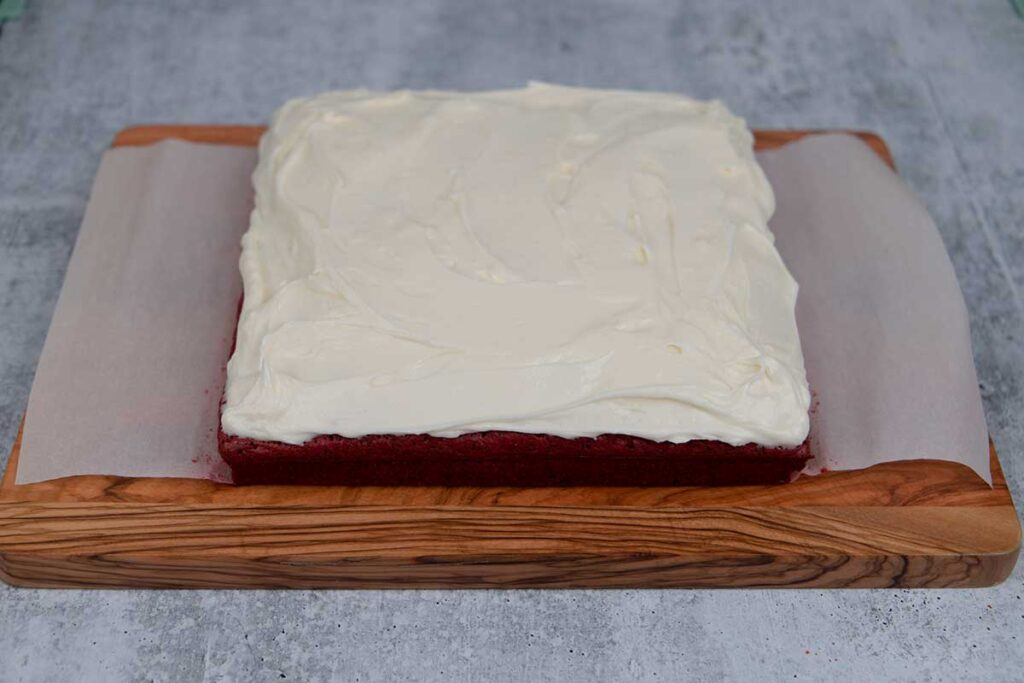 frosted red velvet brownies on a wooden board