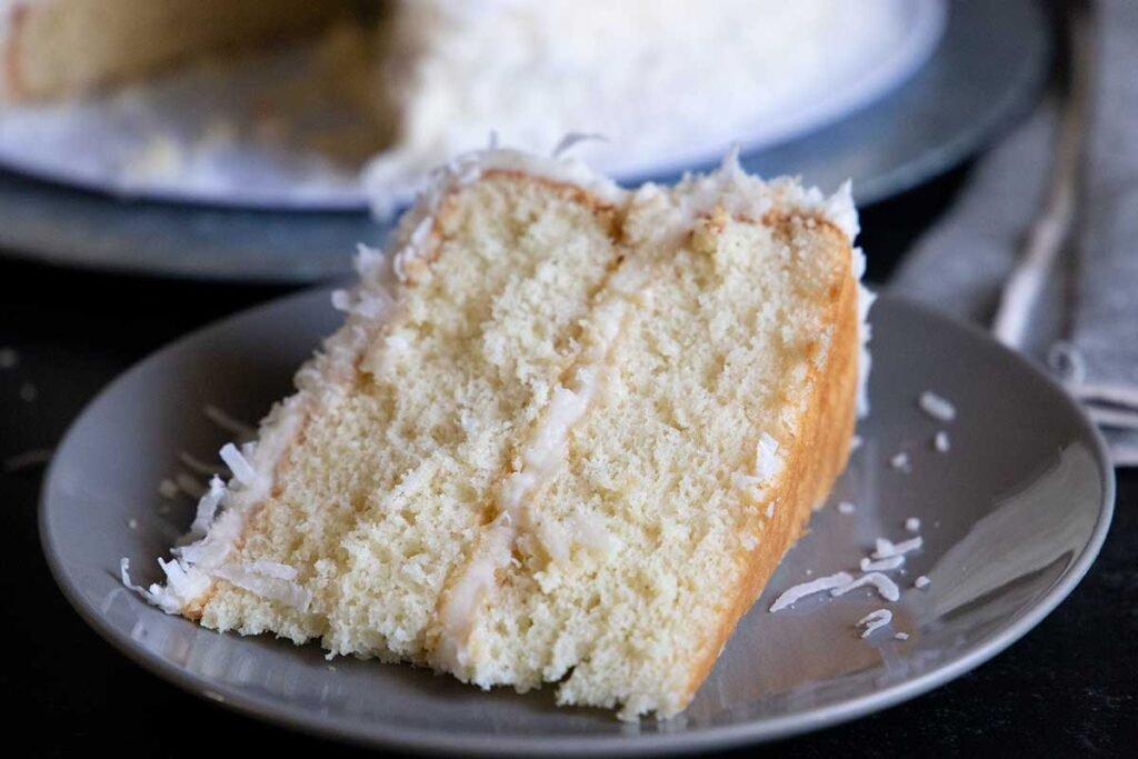 slice of coconut cake on gray plate