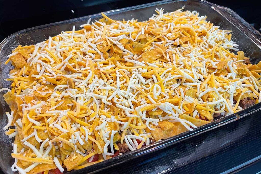 Frito pie casserole assembled and ready for baking