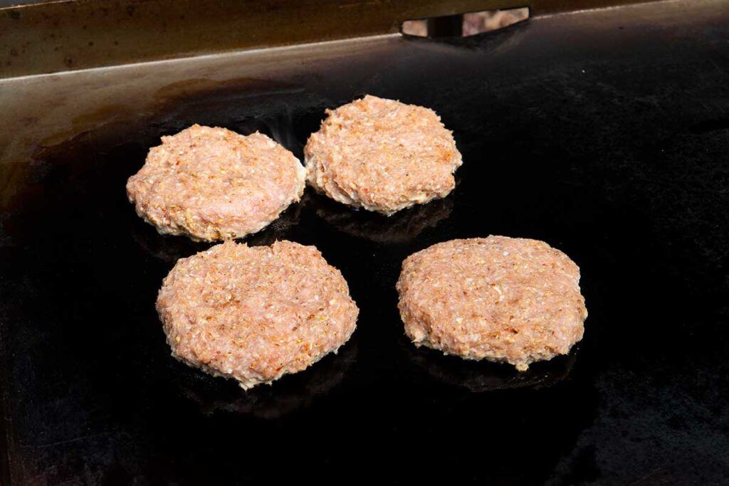 Four turkey burgers cooking on a flat top griddle