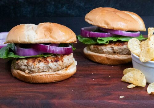 Two turkey burgers with lettuce and red onion on a cutting board