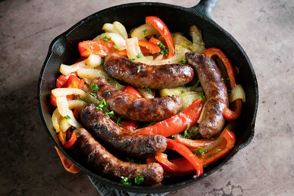 beer brats with peppers and onions, cooked, in a cast iron skillet