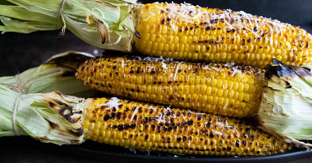 Grilled corn on the cob, topped with shredded parmesan cheese on a black plate.
