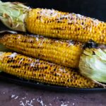Grilled corn on the cob on a black plate