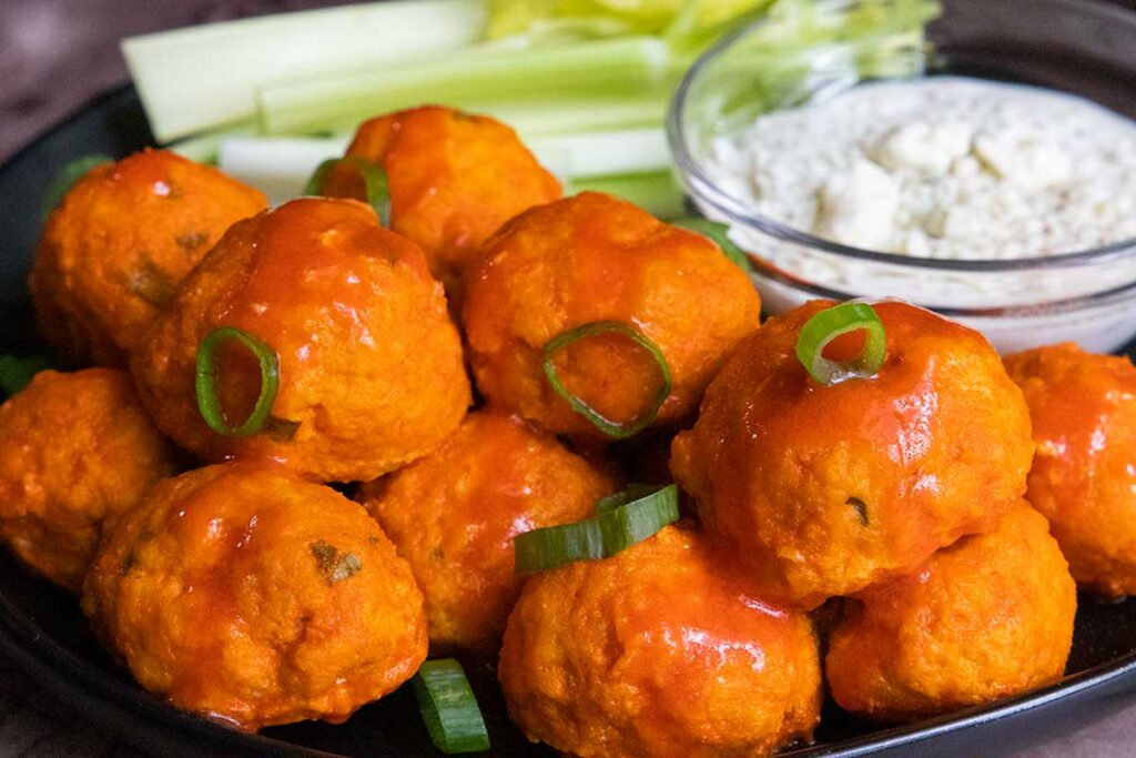 Buffalo chicken meatballs with a green onion garnish