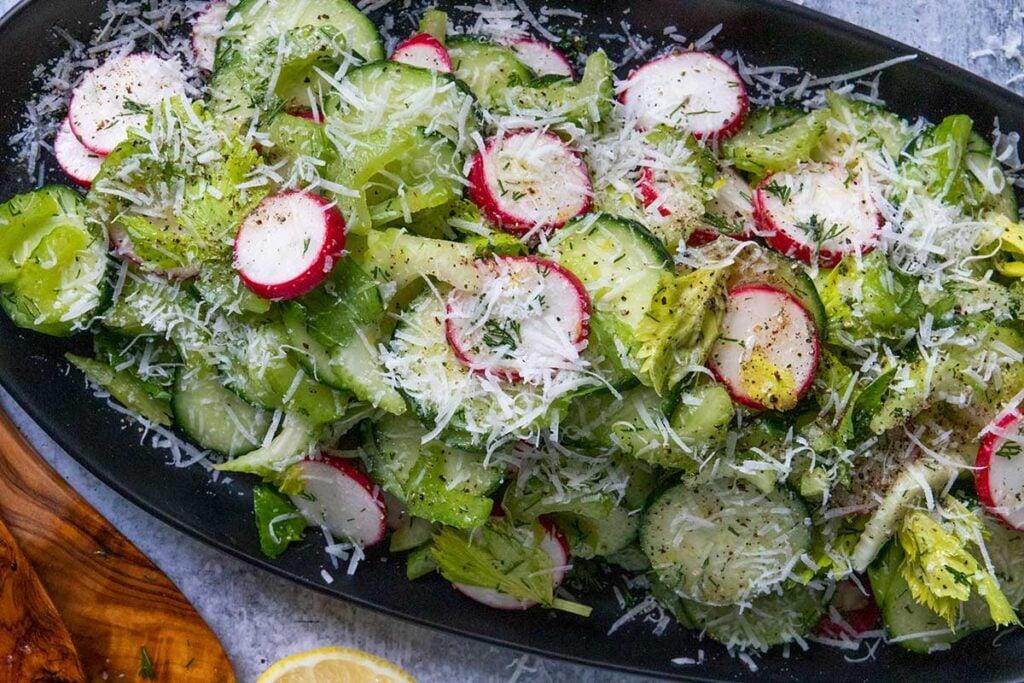 cucumber radish salad on a black platter