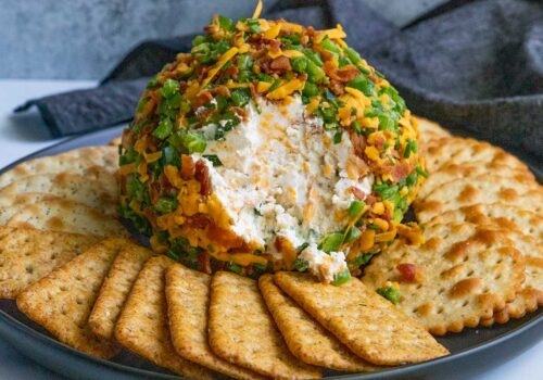 Jalapeno Popper Cheese Ball on a black plate with crackers