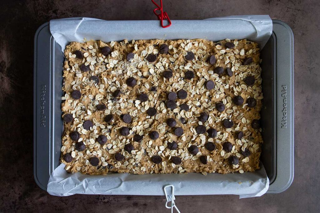 oatmeal chocolate chip cookie bar dough in a parchment lined baking pan