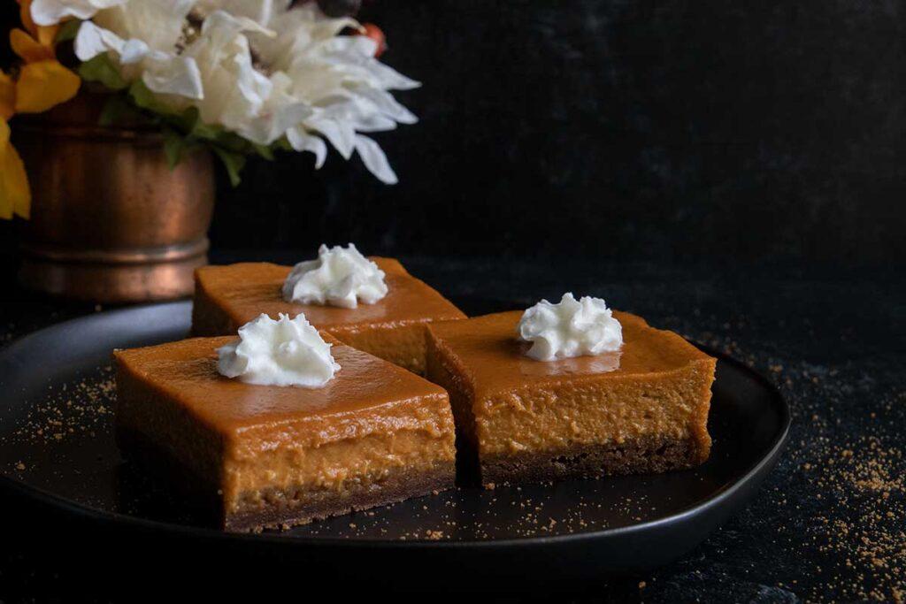 pumpkin pie bars on a black plate