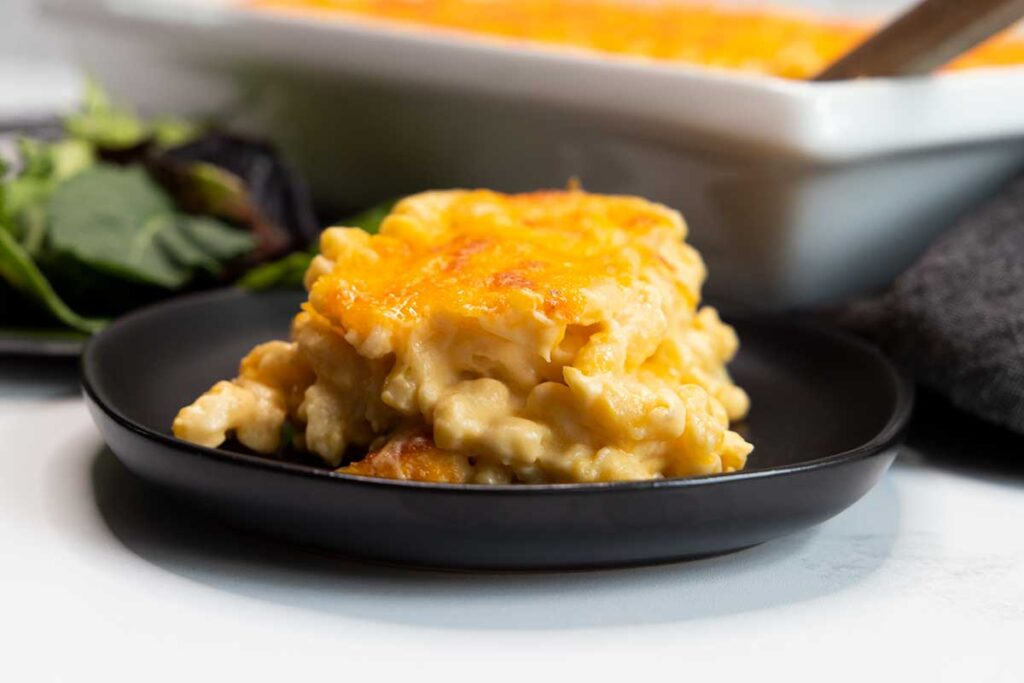 A serving of baked macaroni and cheese on a black plate