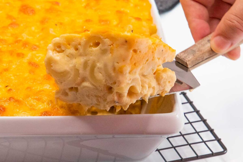 Getting a portion of baked macaroni and cheese out of the baking dish