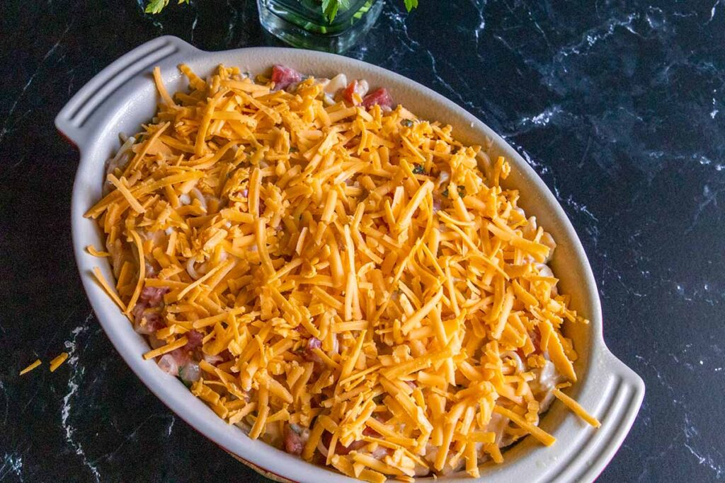 unbaked chicken spaghetti in a casserole topped with shredded cheese