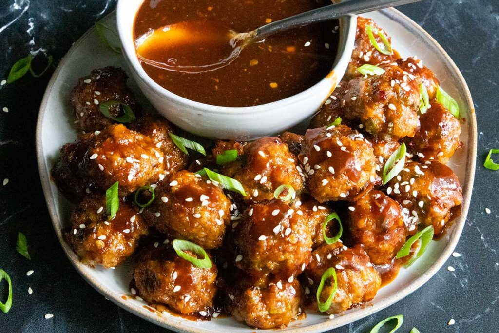 sweet and spicy meatballs on a plate with dipping sauce