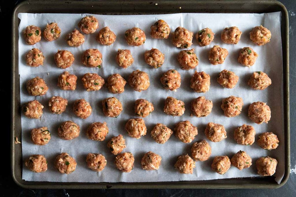 tiny meatballs on a parchment lined baking sheet