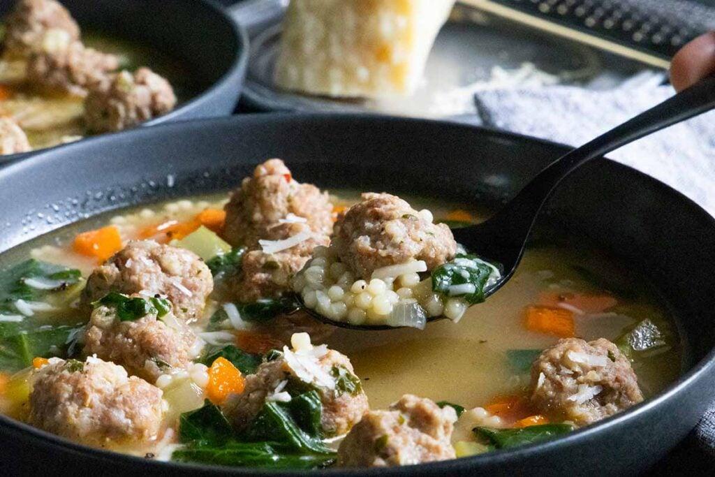 Italian wedding soup on a black spoon